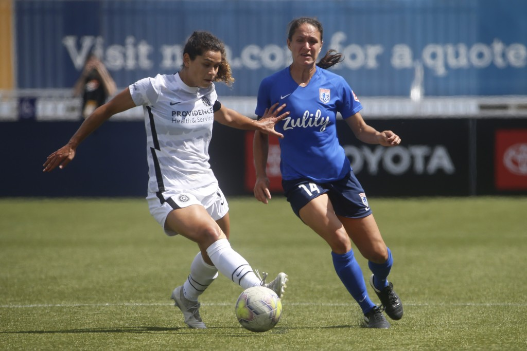 Portland Thorns midfielder Rocky Rodriguez, left, and OL Reign defender Steph Cox (14) battle for the ball during the first half of an NWSL Challenge ...