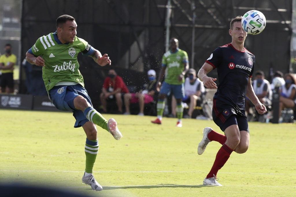 Seattle Sounders midfielder Miguel Ibarra, left, takes a shot on goal as Chicago Fire midfielder Fabian Herbers, right, tries to defend during the fir...