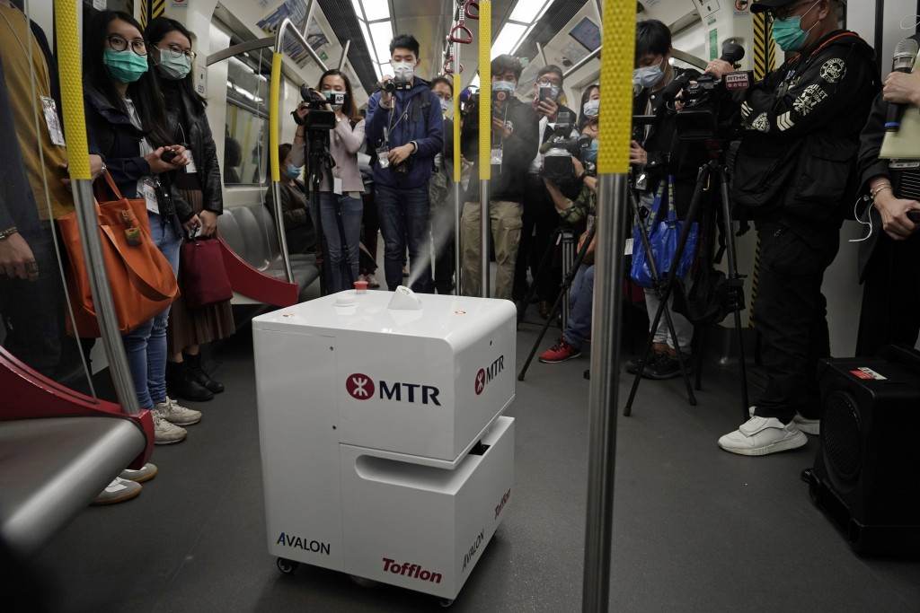 FILE - In this March 11, 2020, file photo, members of the media attend a news conference as a robot sprays hydrogen peroxide during a demonstration in...