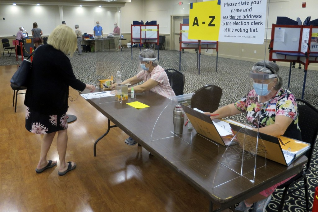 Election workers Adonlie DeRoche, seated left, and Judy Smith, seated right, wear masks and face shields and work behind plexiglass for safety during ...
