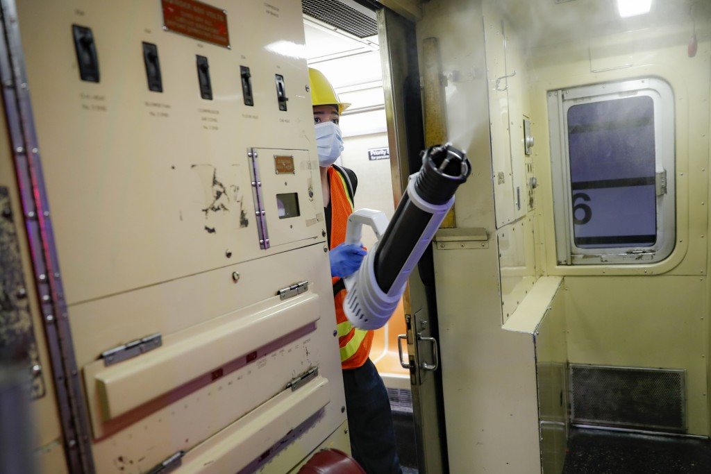 A contractor cleans a subway car at the 96th Street station to control the spread of COVID-19, Thursday, July 2, 2020, in New York. Mass transit syste...