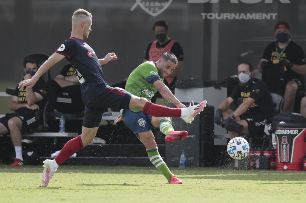 Seattle Sounders midfielder Nicolas Lodeiro, right, takes a shot on goal as Chicago Fire midfielder Fabian Herbers, left, tries to block the shot duri...
