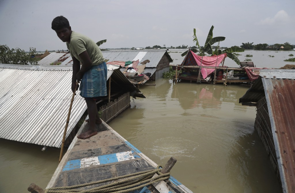 A man rows a boat near his submerged house in Gagolmari village, in Morigaon district of Assam, India, Tuesday, July 14, 2020. Hundreds of thousands o...