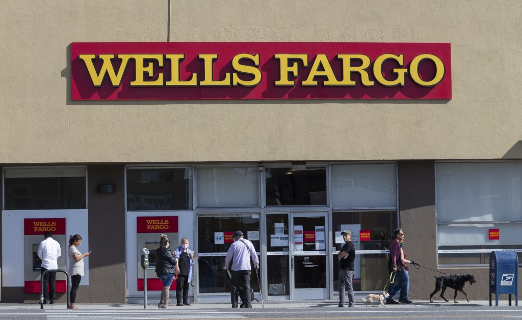 FILE - In this April 3, 2020, file photo, customers, some wearing face masks, line up outside a Wells Fargo branch in the Atwater Village neighborhood...