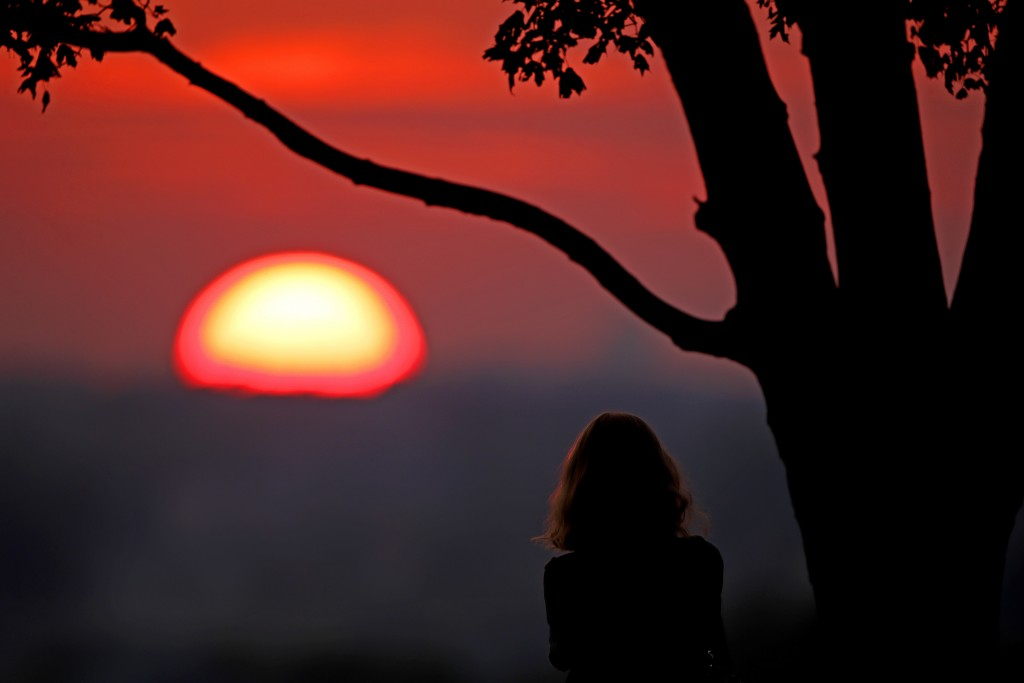 FILE - In this  July 3, 2020, file photo, a woman watches the sunset from a park in Kansas City, Mo. 2020 is barely halfway over. That hasn't stopped ...