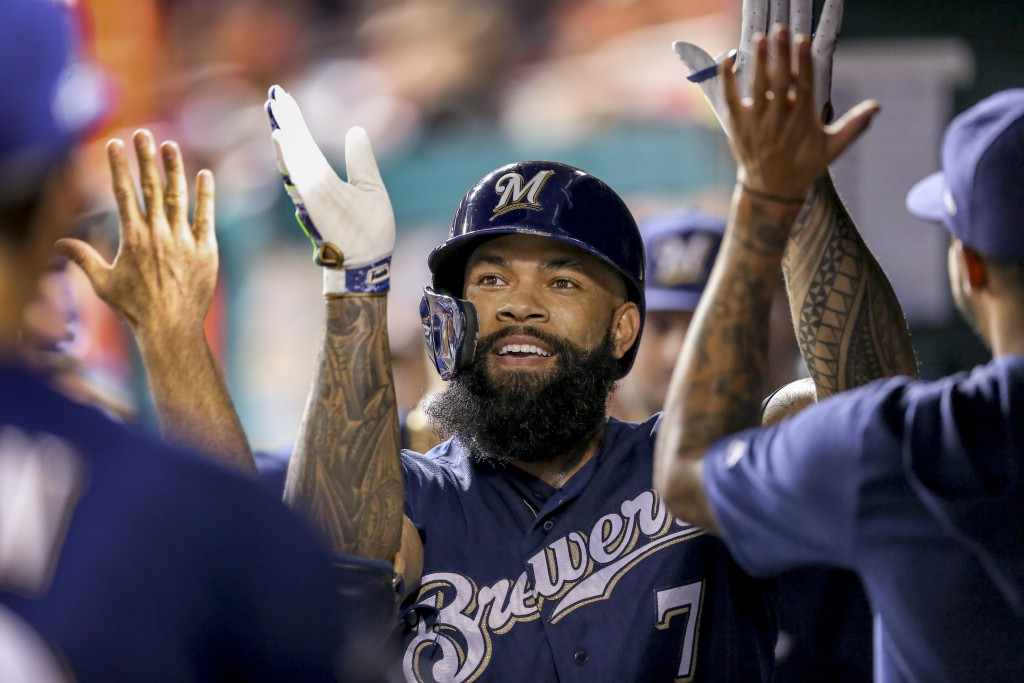 FILE - In this Oct. 1, 2019, file photo, Milwaukee Brewers' Eric Thames high fives teammates after hitting a solo home run during the second inning of...