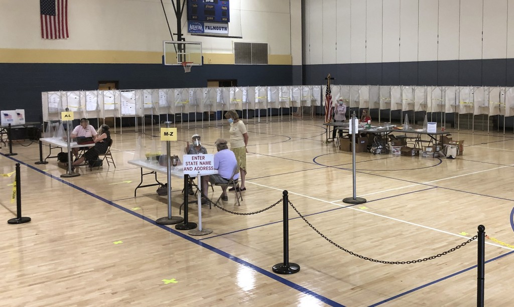 Election workers deal with a light voter turnout for primary elections at Falmouth High School on Tuesday, July 14, 2020, in Falmouth, Maine. Voters w...