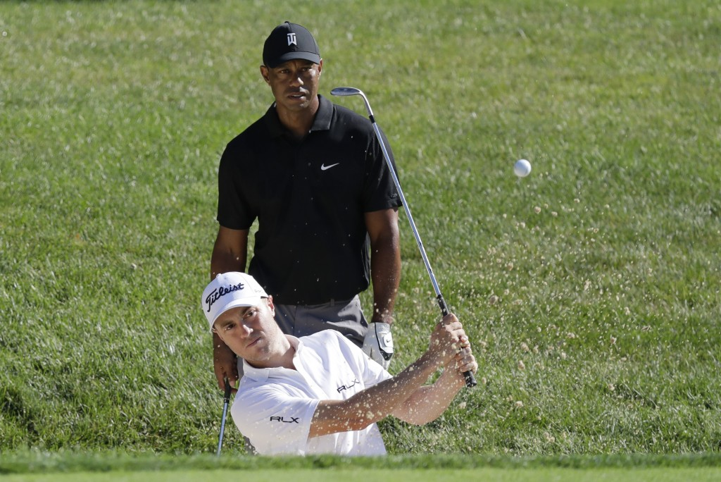 Justin Thomas hits out of a bunker on the 15th hole as Tiger Woods watches during a practice round for the Memorial golf tournament, Tuesday, July 14,...