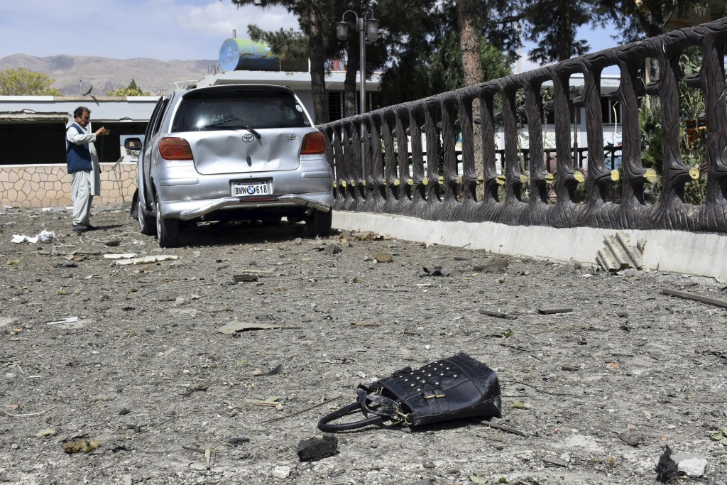 A man takes pictures at the site of a car bomb blast on an intelligence compound in Aybak, the capital of the Samangan province in northern Afghanista...