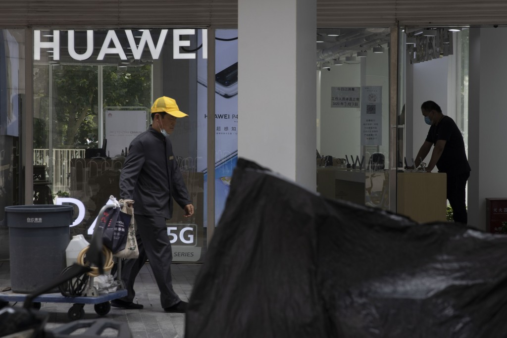 A worker pulls a trolley past a man looking at phones displayed at a Huawei store in Beijing Monday, July 13, 2020. Huawei Technologies reported Tuesd...