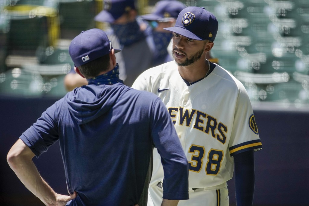 Milwaukee Brewers' Devin Williams talks to manager Craig Counsell during a practice session Monday, July 13, 2020, at Miller Park in Milwaukee. (AP Ph...