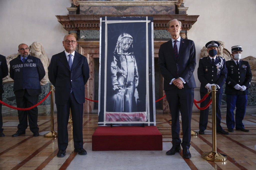 Franch Ambassador to Italy, Christian Masset, right, and Italian prosecutor Michele Renzo pose next to a recovered stolen artwork by British artist Ba...