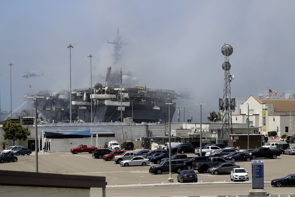 A helicopter drops water on the USS Bonhomme Richard as crews fight the fire Monday, July 13, 2020, in San Diego. Fire crews continue to battle the bl...