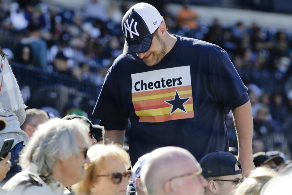 FILE - In this Feb. 29, 2020, file photo, a New York Yankees fan, wearing a T-shirt mocking the Houston Astros, takes his seat during the sixth inning...