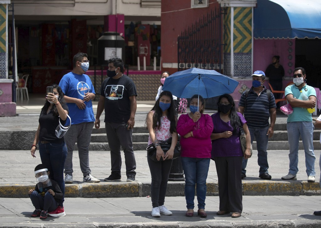 Relatives of Mexican citizens that died from COVID-19 complications in the United States attend a ceremony for their loved ones in Puebla, Mexico, Mon...