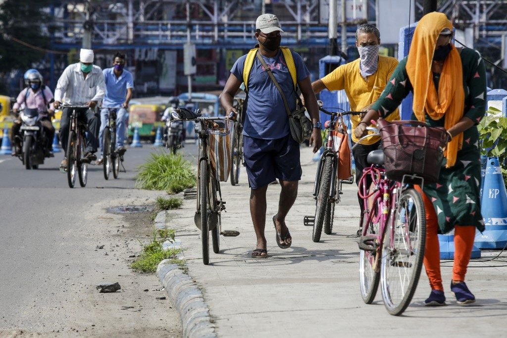 People wearing face masks cross a bridge with their cycles in Kolkata, India, Tuesday, July 14, 2020. Several Indian states imposed weekend curfews an...