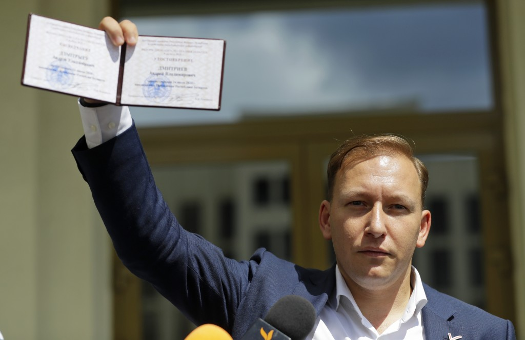 Andrei Dmitriyev shows his presidential candidate's identification card after he was registered as a candidate for the presidential elections in Minsk...
