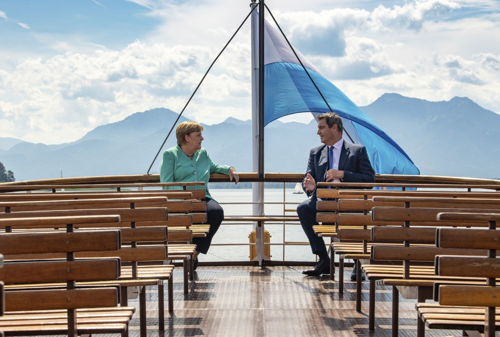 German Chancellor Angela, left, and Markus Soeder, right, Governour of the German state of Bavaria, talk during a boat tour in Priem Am Chiemsee, Germ...