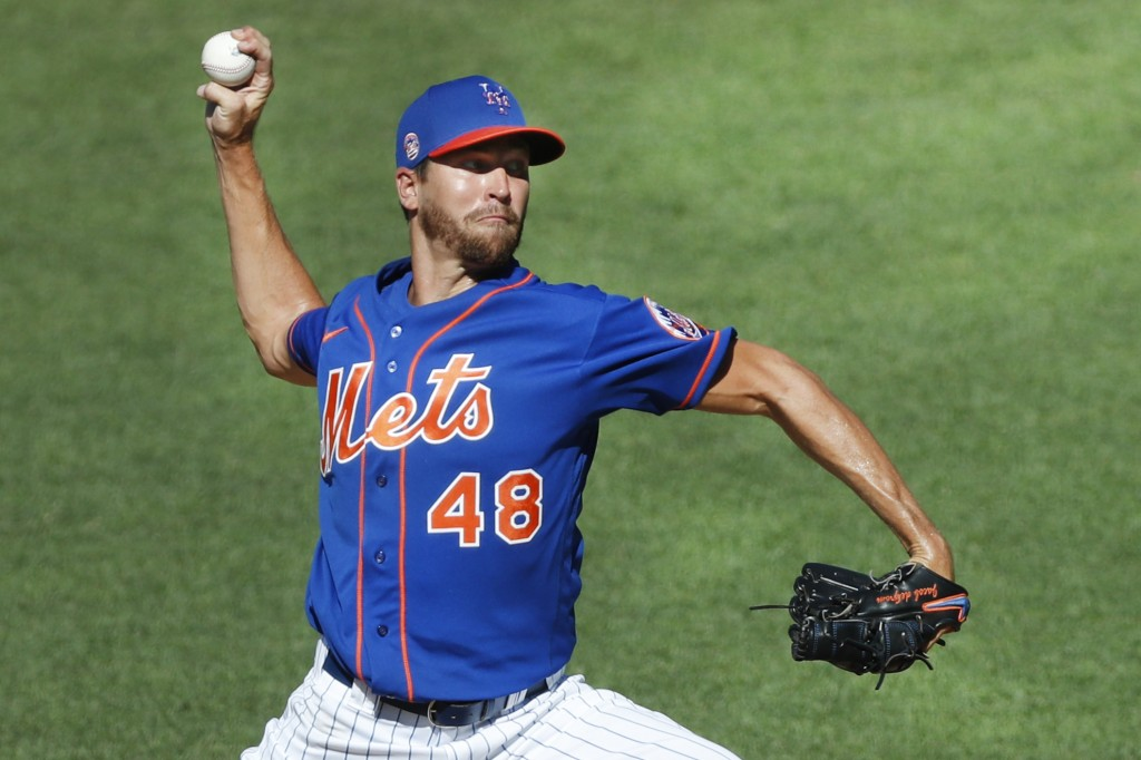 FILE - In this July 9, 2020, file photo, New York Mets starting pitcher Jacob deGrom winds up while delivering during a simulated baseball game, part ...