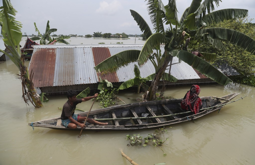 An Indian flood affected man and a woman ride on a country boat in Gagolmari village, Morigaon district, Assam, India, Tuesday, July 14, 2020. Hundred...