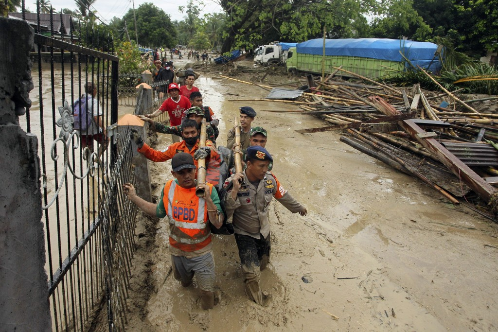 Rescuers wade through mud as they carry the body of a victim at an area affected by flash flood in Baebunta, South Sulawesi province, Indonesia, Tuesd...