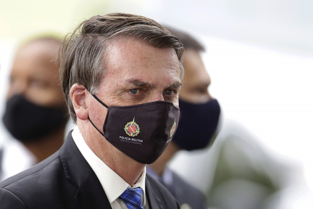 FILE - In this May 18, 2020, file photo, Brazilian President Jair Bolsonaro wears a mask due to the coronavirus pandemic as he talks with supporters u...