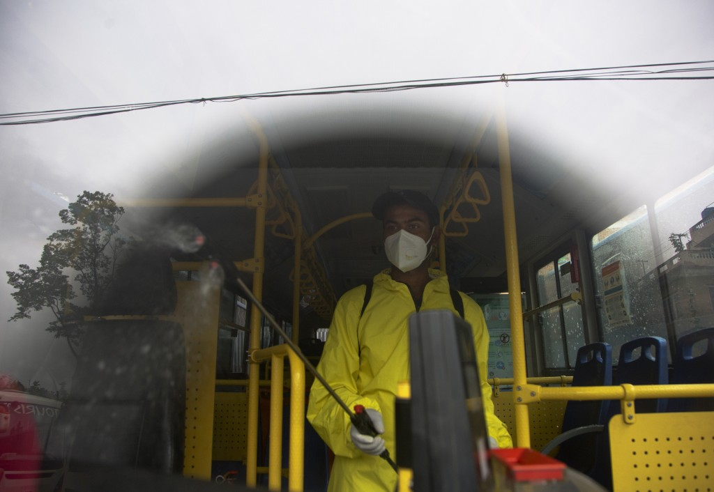 A Nepalese bus driver disinfects his vehicle before starting service in Kathmandu, Nepal, Tuesday, July 14, 2020. After restrictions on public transpo...