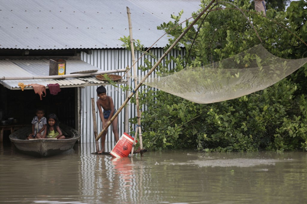 An Indian flood affected boy fishes as two children sit on a country boat near their partially submerged house in Gagolmari village, Morigaon district...
