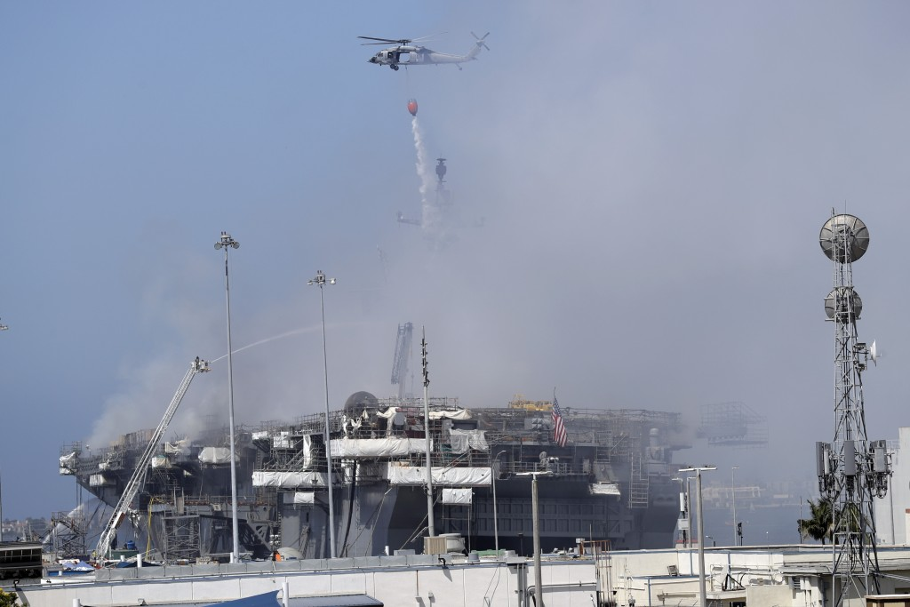 A helicopter drops water on the USS Bonhomme Richard, Monday, July 13, 2020, in San Diego. Fire crews continue to battle the blaze Monday after 21 peo...