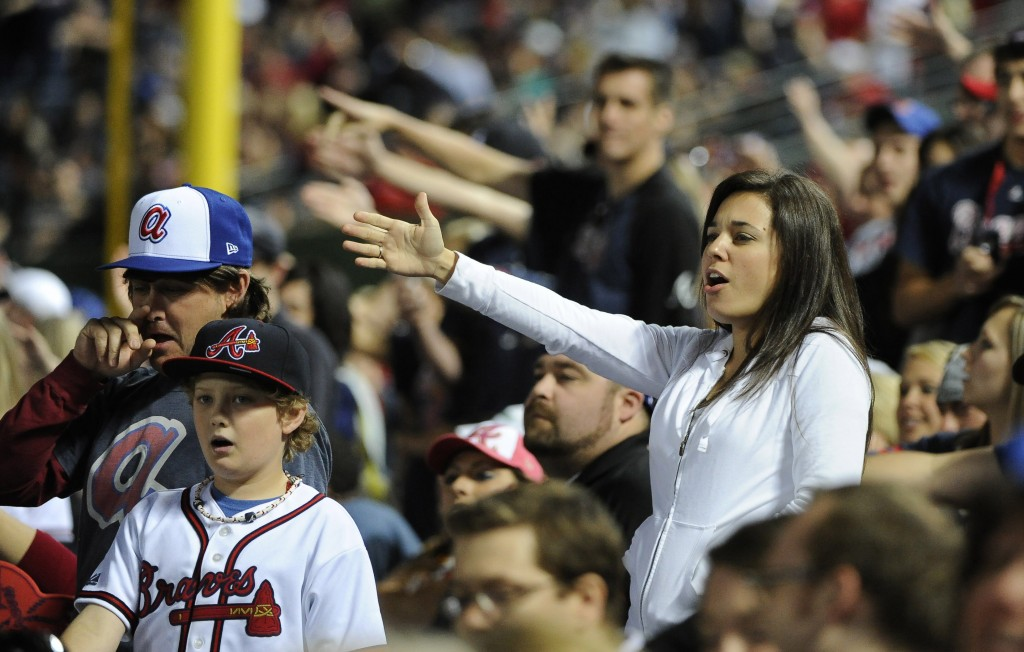 FILE - In this May 2, 2014, file photo, Atlanta Braves fans do the tomahawk chop during the ninth inning of a baseball game with the San Francisco Gia...