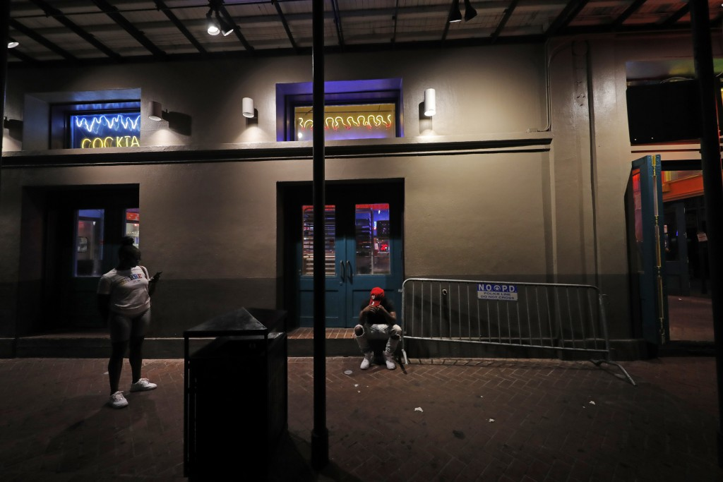 People are seen outside a bar with no customers on Bourbon Street in the French Quarter of New Orleans, Tuesday, July 14, 2020. Many bars are closed a...