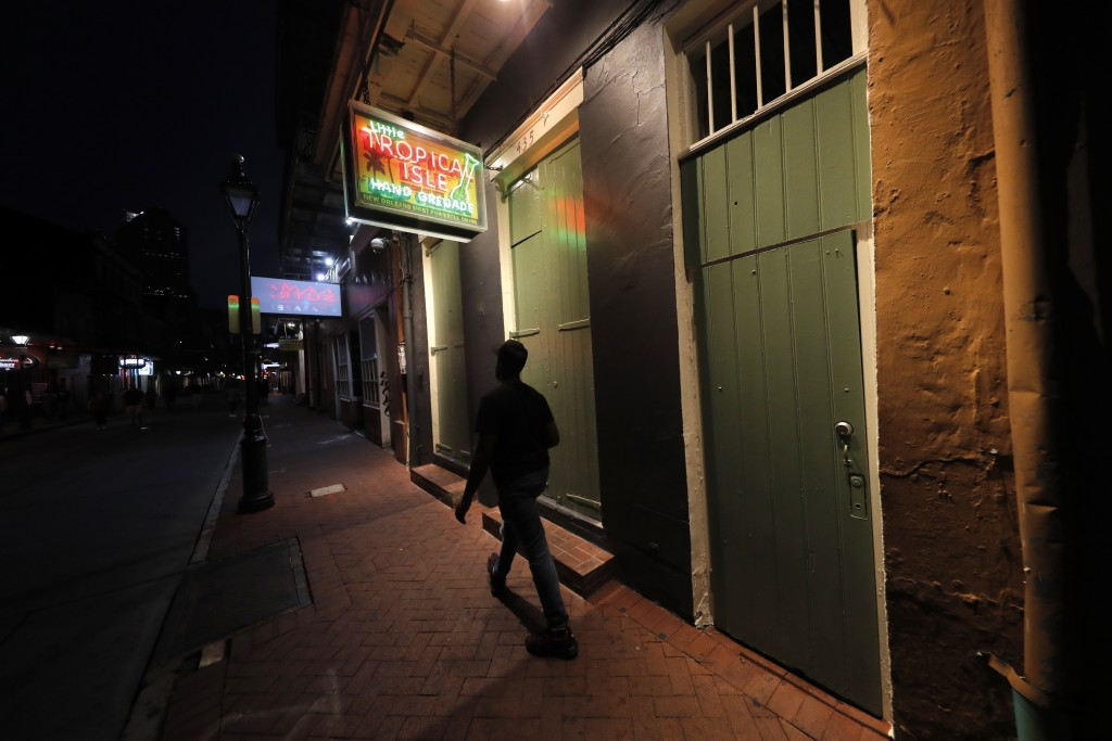 A man walks by the closed Tropical Isle Bar on Bourbon Street in the French Quarter of New Orleans, Tuesday, July 14, 2020. A sharp increase in COVID-...