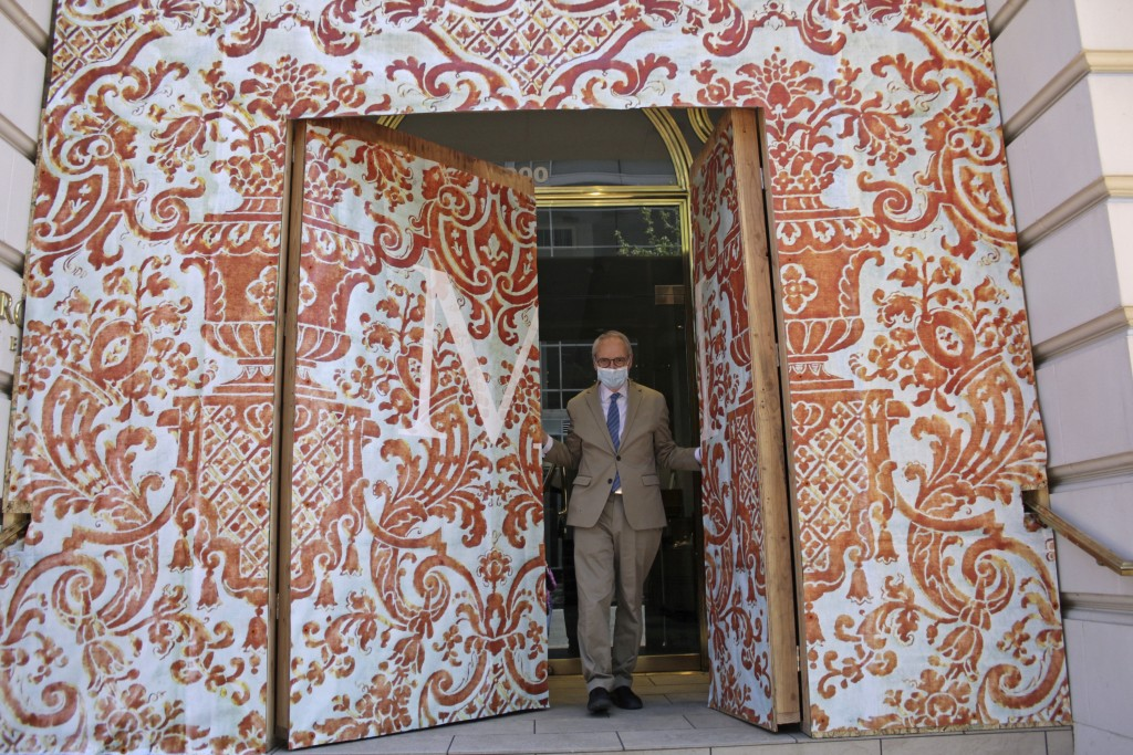 David Margulis, owner of Margulis Jewelers, emerges from a double layer of plywood doors he had installed to protect his store from protests that have...