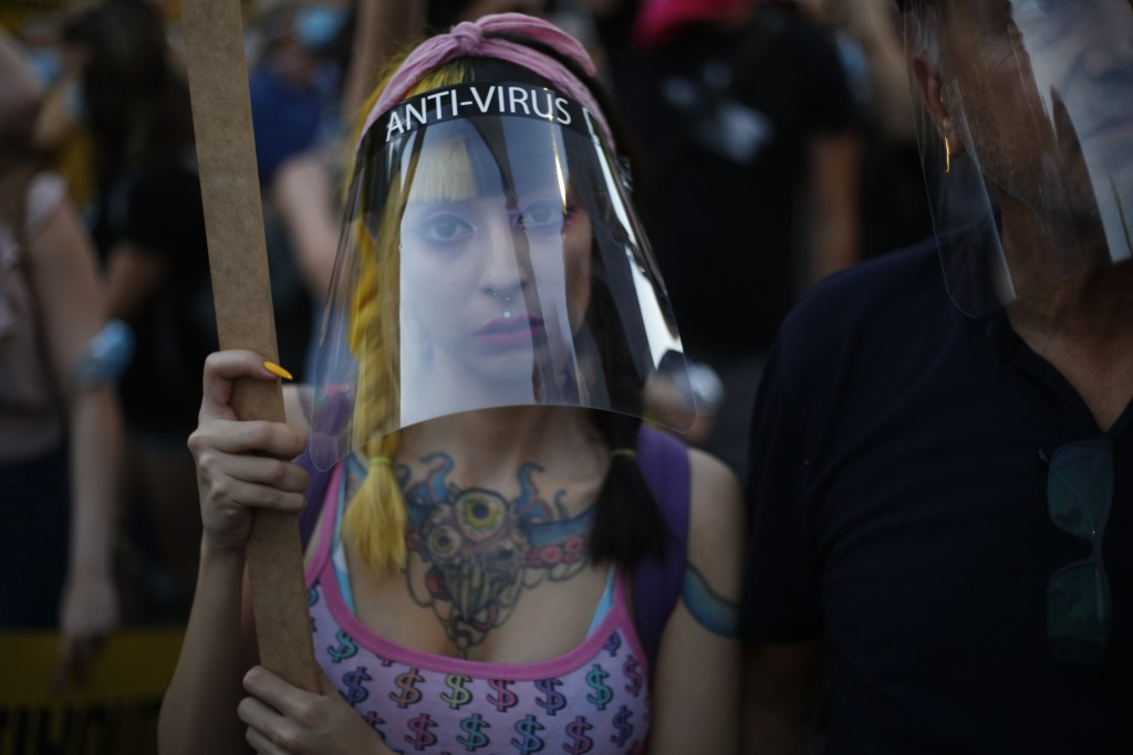 A protester wears a face mask to curb the spread of the coronavirus outside of the Prime Minister's residence in Jerusalem, Tuesday, July 14, 2020. Th...