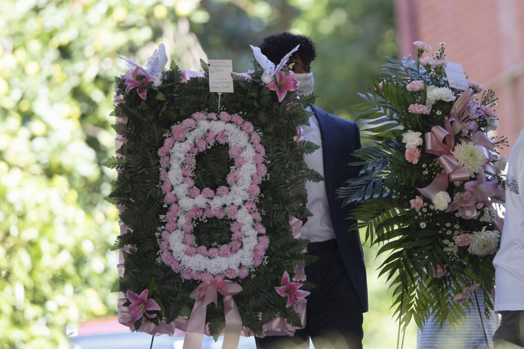 A man carries flowers into a viewing for 8-year-old Secoriea Turner, who was fatally shot in Atlanta on July 4th near the Wendy's site where Rayshard ...