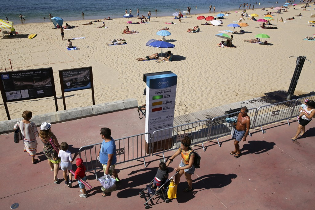People arrive at the beach walk past a semaphore system that signals how crowded the beach is at any moment, in Oeiras, outside Lisbon, Wednesday, Jul...