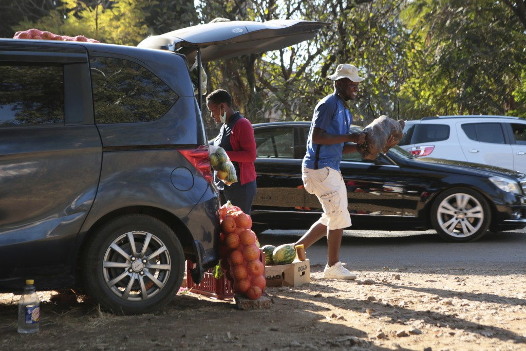 A man carries a bag of potatoes to a customer while selling them from his car by the side of a busy road in Harare, Zimbabwe, Tuesday, June, 23, 2020....