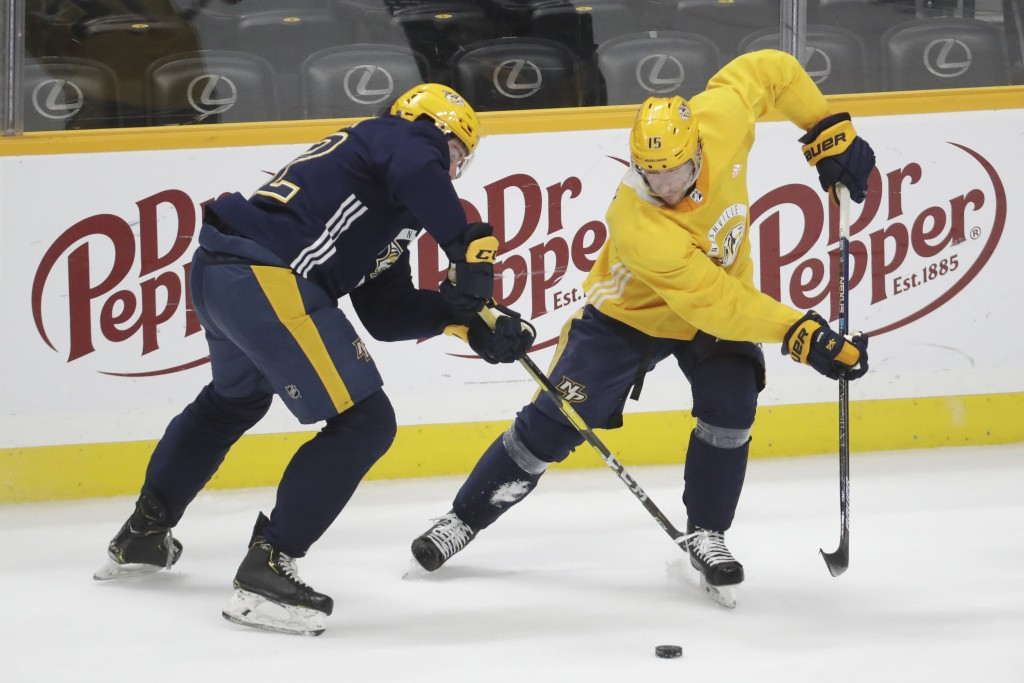 Nashville Predators center Yakov Trenin, of Russia, left, and right wing Craig Smith (15) battle for the puck during NHL hockey training camp Tuesday,...