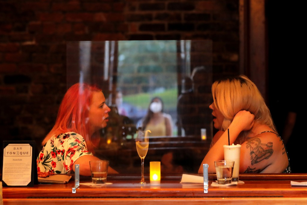 A masked patron's reflection is seen in a plexiglass partition, as other patrons chat inside Bar Tonique in New Orleans, Thursday, July 9, 2020. A sha...
