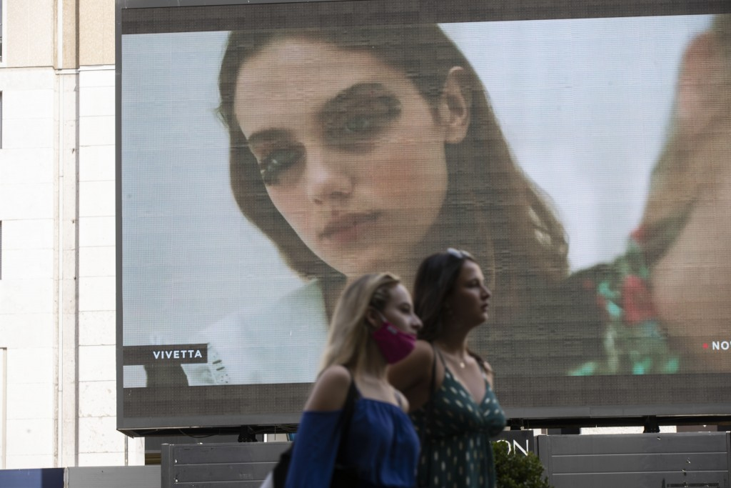 Pedestrians pass by a screen showing a Vivetta model during the Milan Digital Fashion Week, in Milan, Italy, Tuesday, July 14, 2020. Forty fashion hou...