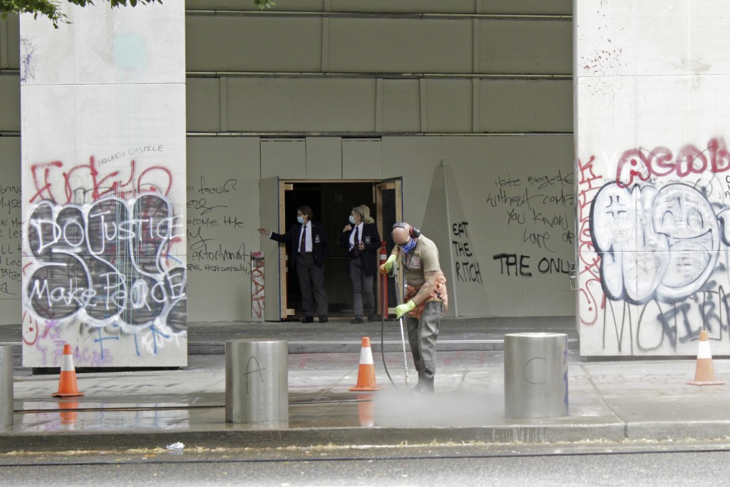 FILE - In this July 8, 2020, file photo, a worker washes graffiti off the sidewalk in front of the Mark O. Hatfield Federal Courthouse in downtown Por...