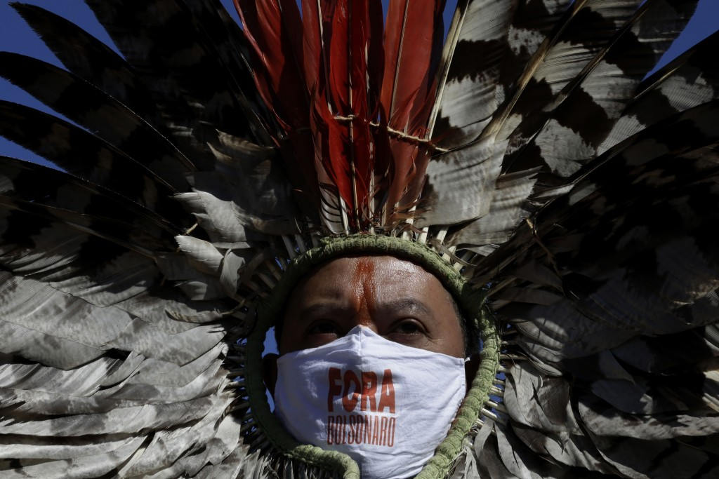 """Indigenous leader Kretan Kaingang wears a face mask with a hashtag that reads in Portuguese: """"Get out Bolsonaro"""" during a protest demanding President ..."""