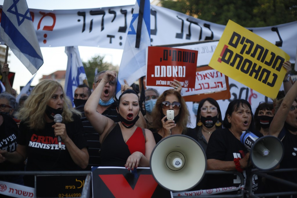 Demonstrators, defying orders to maintain social distancing requirements, chant slogans outside of the Prime Minister's residence in Jerusalem, Tuesda...