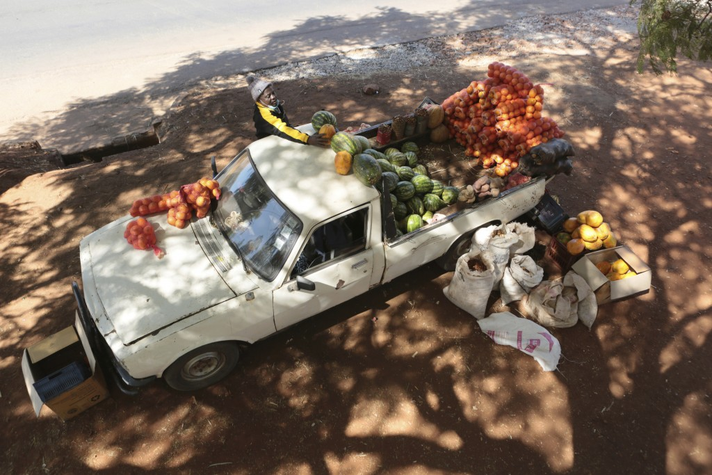 A man lays fruit and vegetables on top of his vehicle while selling them by the side of a busy road in Harare, Zimbabwe, Saturday, July 4, 2020. Cars ...