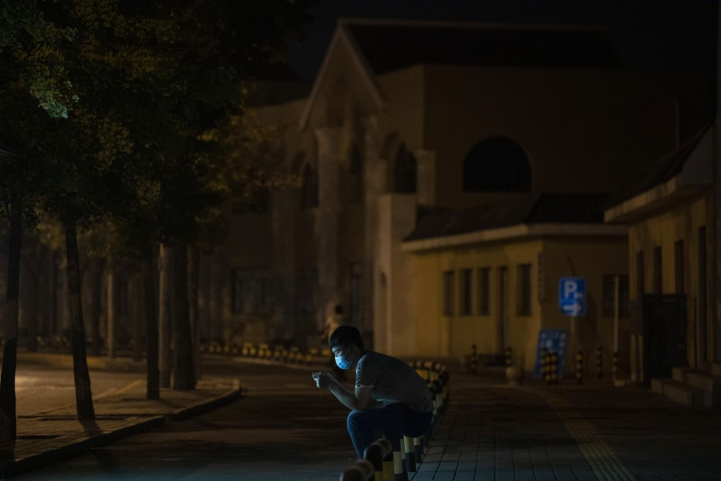 A man wearing a face mask to curb the spread of the coronavirus looks at his smart phone along a dark stretch of road in Beijing, China, Tuesday, July...