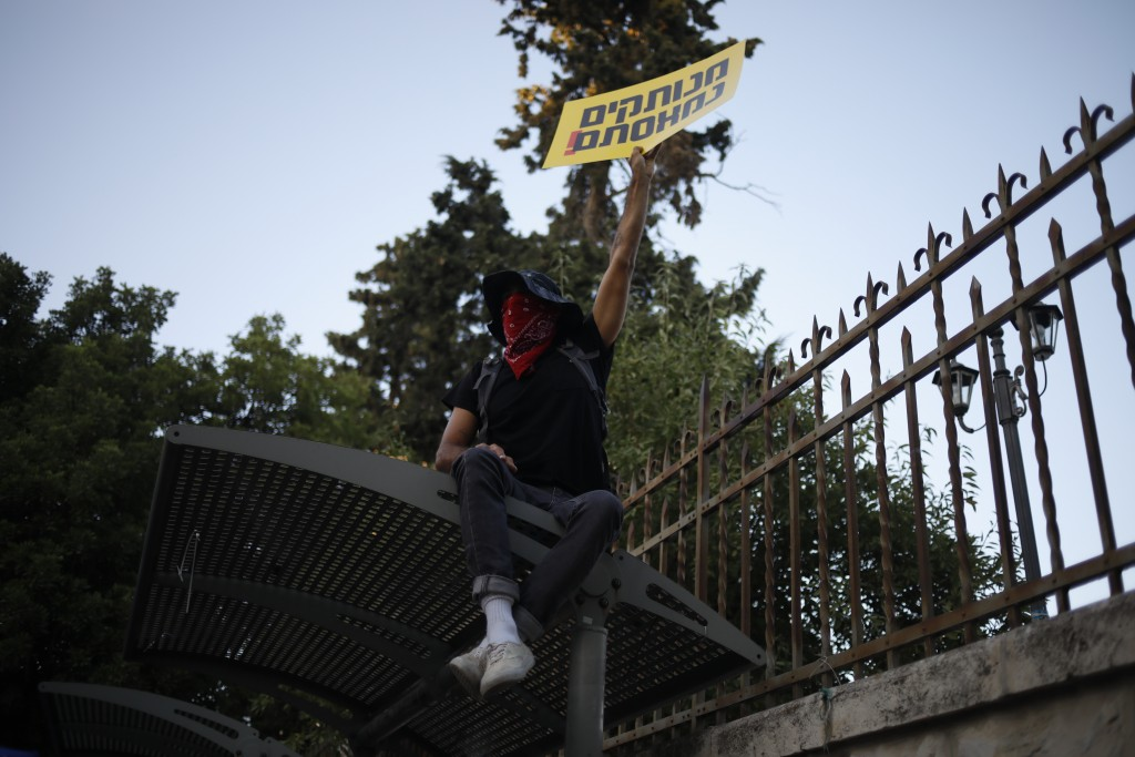"""A protester holds a sign that reads """"you are detached. We are fed up,"""" outside of the Prime Minister's residence in Jerusalem, Tuesday, July 14, 2020...."""
