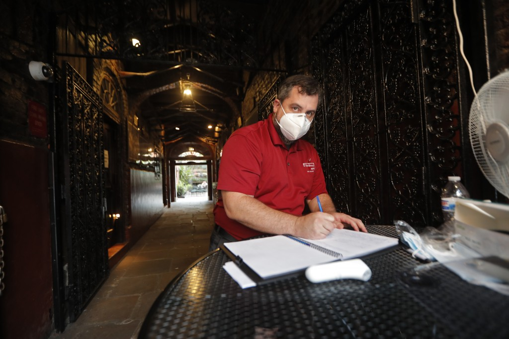 Maitre d' Chad Martin writes the name and phone numbers of patrons entering, after taking their temperature, at Pat O'Briens Bar in the French Quarter...