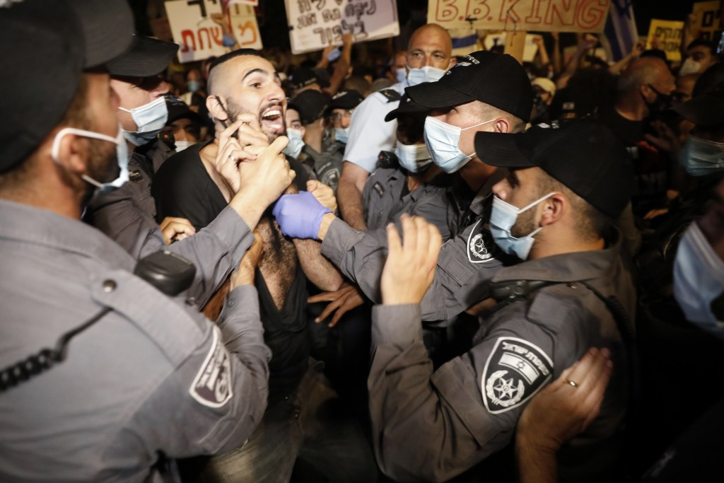 Israeli police officers push a protester outside Prime Minister's residence in Jerusalem, Tuesday, July 14, 2020. Thousands of Israelis on Tuesday dem...