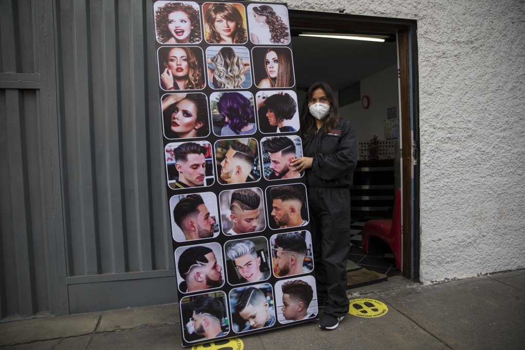 A hairdresser prepares to open his business amid the COVID-19 pandemic, in Lima, Peru, Tuesday, July 14, 2020. (AP Photo/Rodrigo Abd)