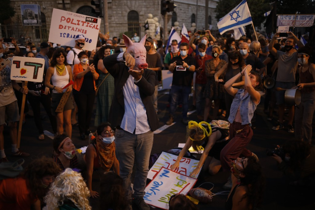 Demonstrators, defying orders to maintain social distancing requirements, chant slogans and blow horns outside Prime Minister's residence in Jerusalem...